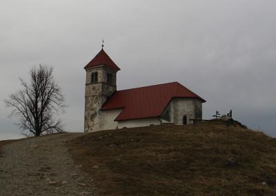 Cerkev sv. Ane se nahaja na manjši razgledni vzpetini nad Jezerom, Podpečjo in Preserjem.